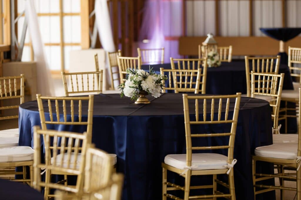 round table with navy blue tablecloth, gold chairs, and small white floral centerpiece